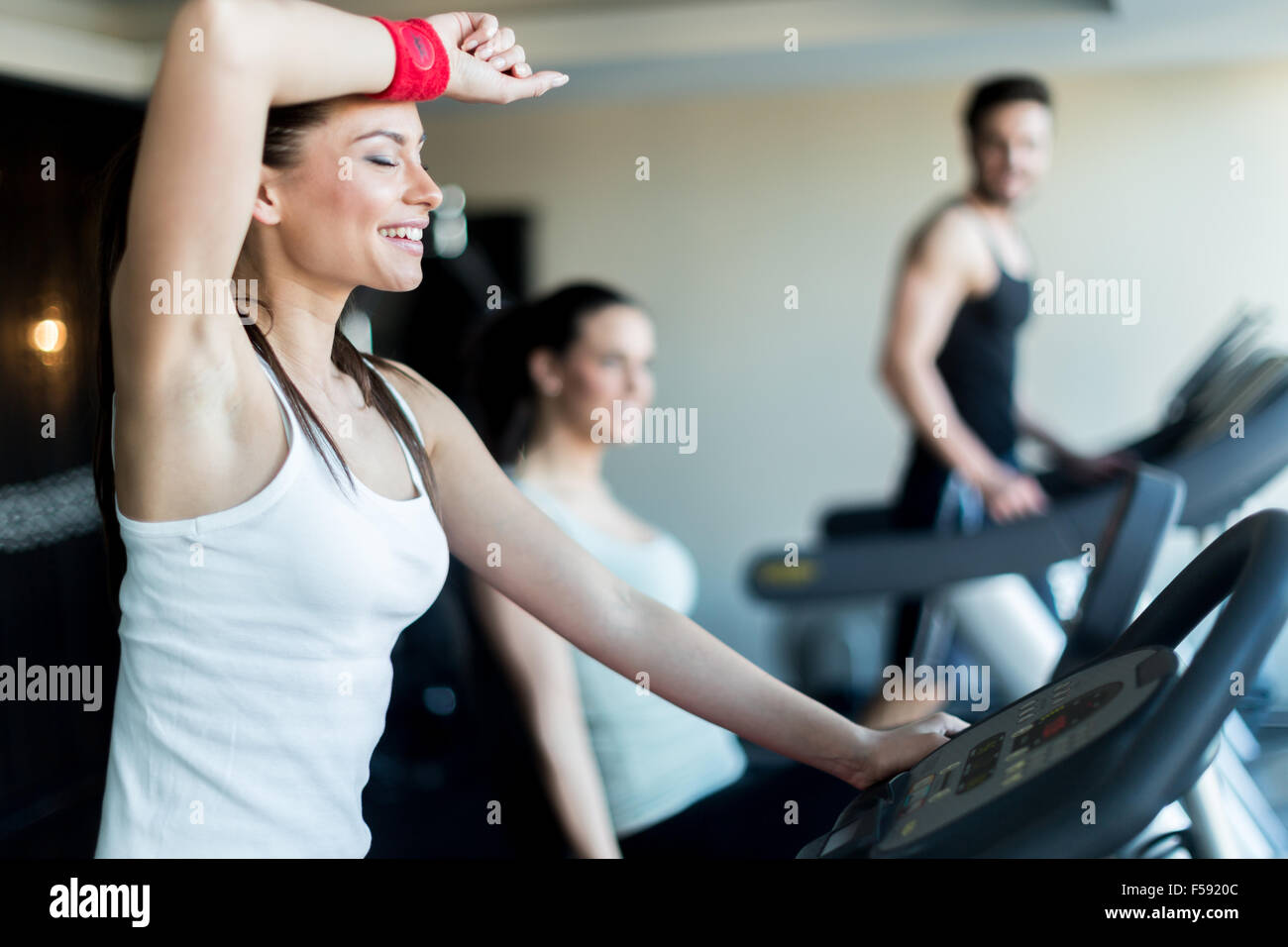 Young, beautiful woman training by riding a bicycle in a gym and sweating - Stock Image