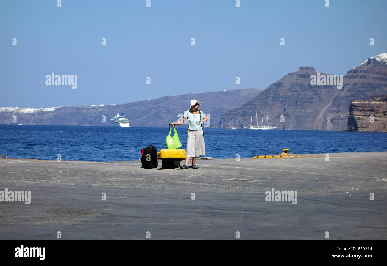 A traveller awaits a ferry in Santorini - Stock Image