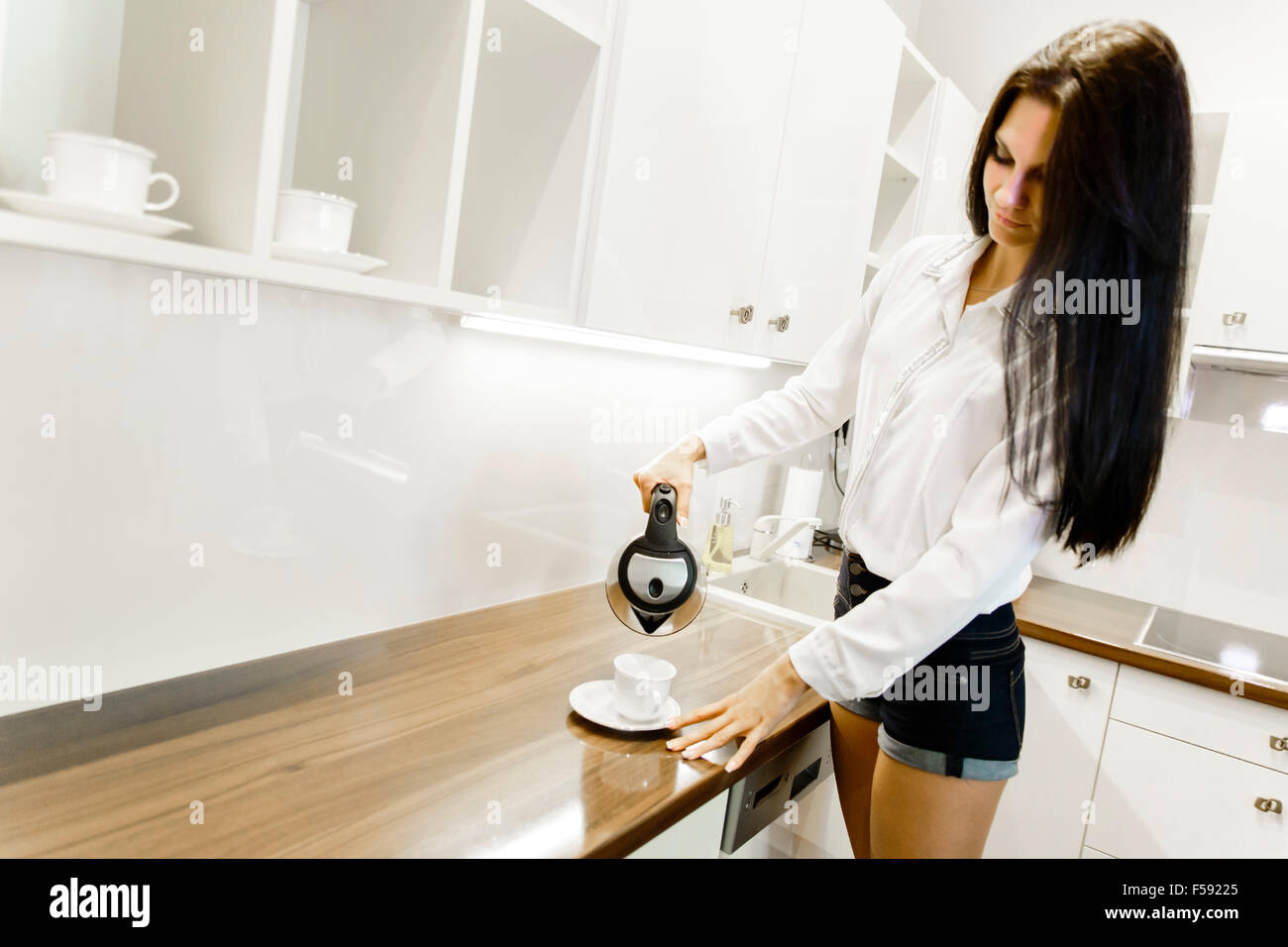 Closeup of hot water being poured out of the kettle in a modern kitchen - Stock Image