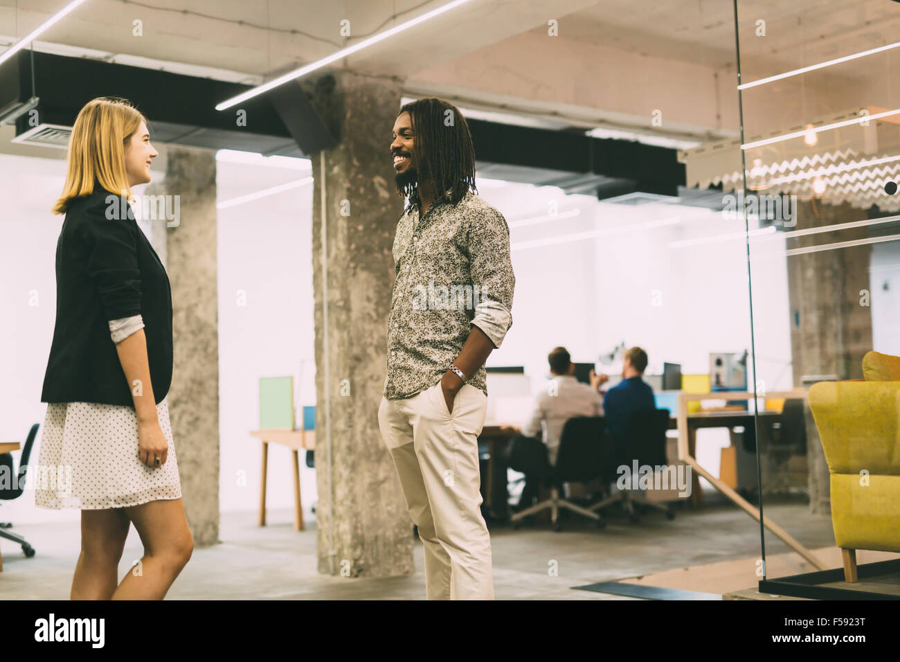 Colleagues talking in office and smiling while standing - Stock Image