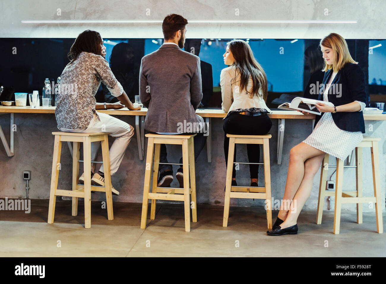 Business people having a break from work and conversing - Stock Image