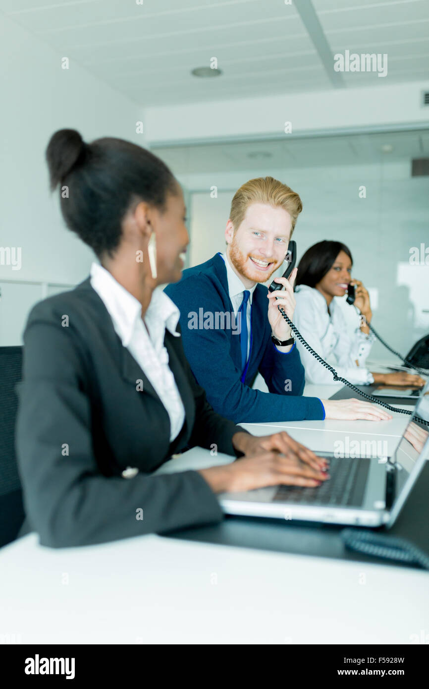 A beautiful, black, young woman working at a call center in an office with her red haird colleague talking to a Stock Photo