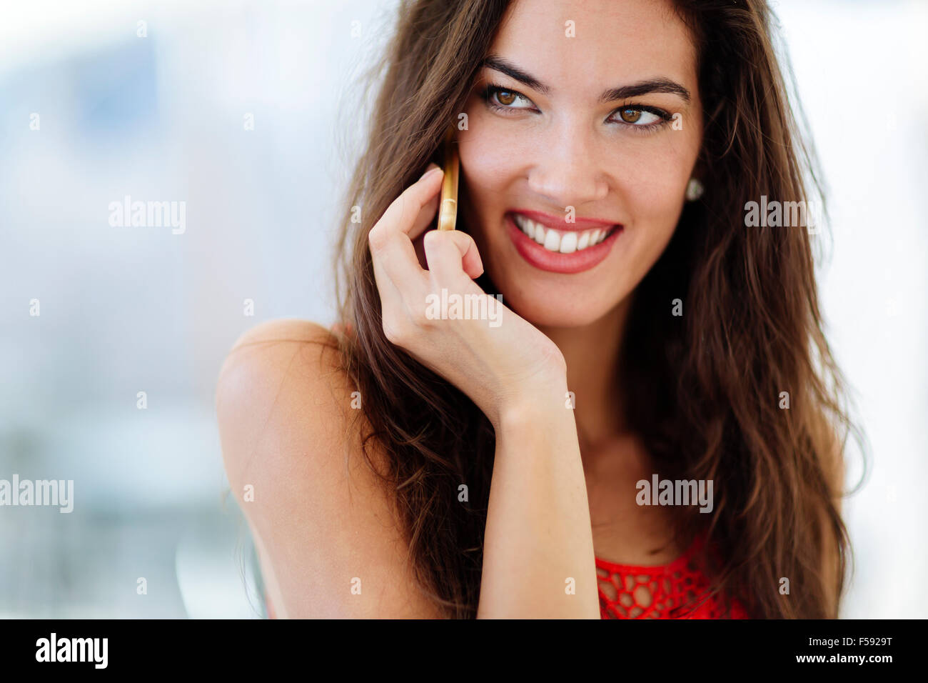 Beautiful model calling on phone and smiling - Stock Image