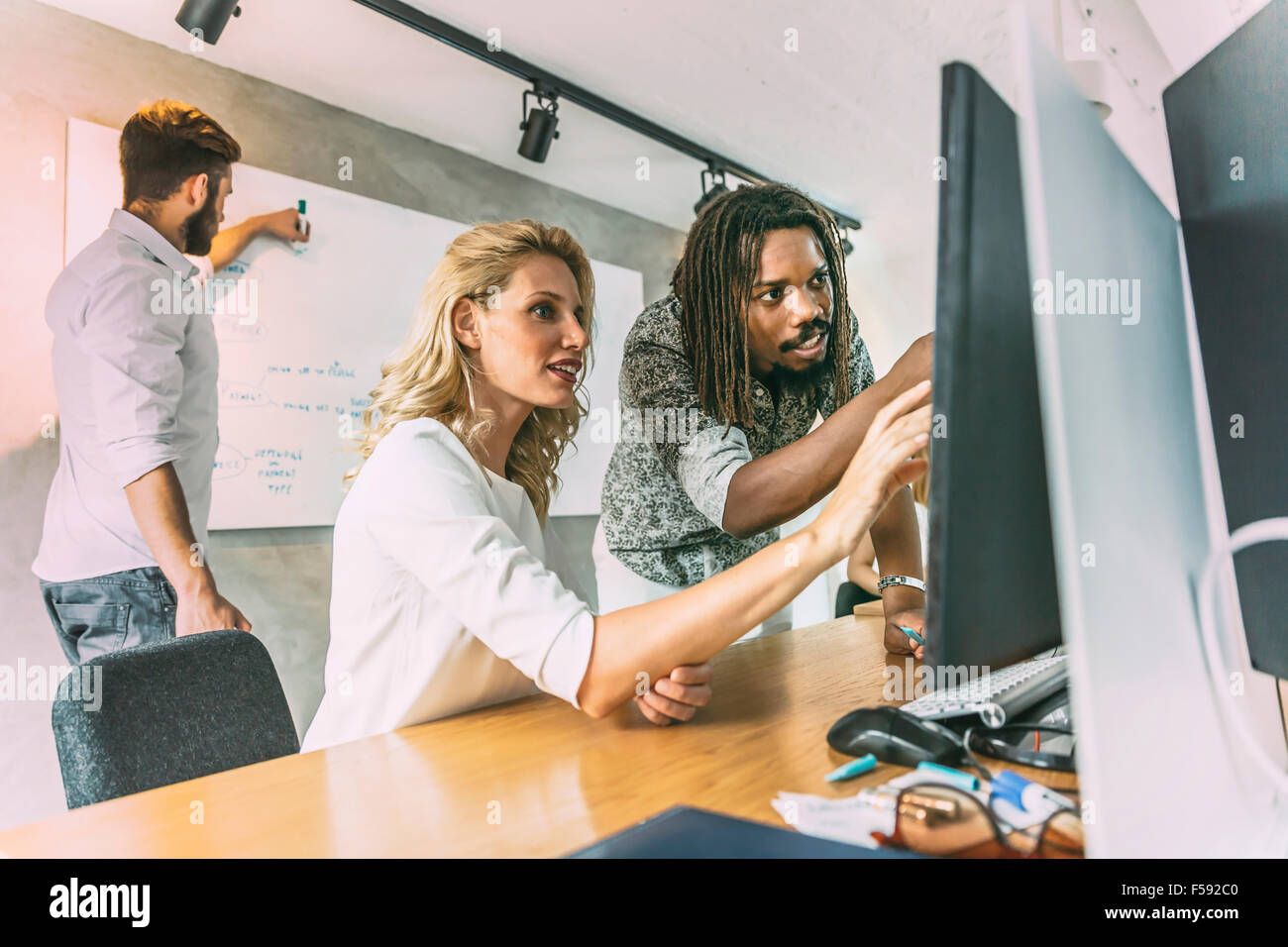 Designer team discussing new ideas and working ona  computer - Stock Image