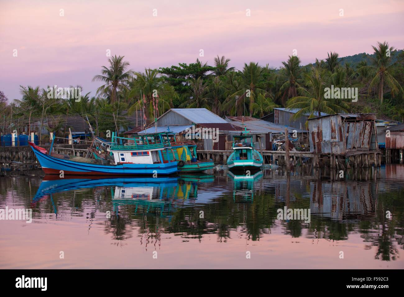 Fishing boats near houses of fishermen in rural area of Phu Quoc Island, Southern Vietnam. - Stock Image