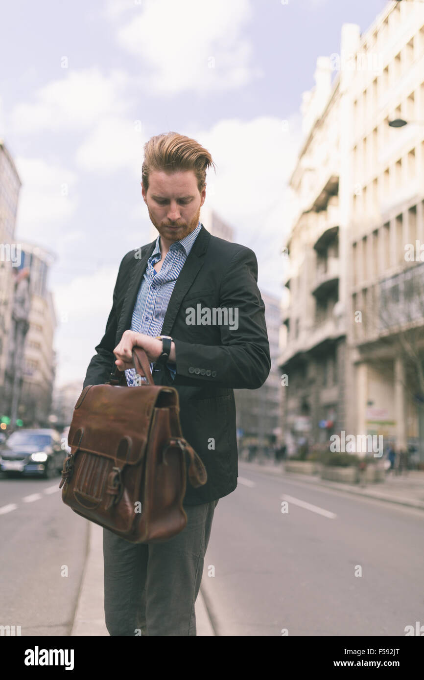 Businessman looking at his wrist watch in the middle of the city road - Stock Image