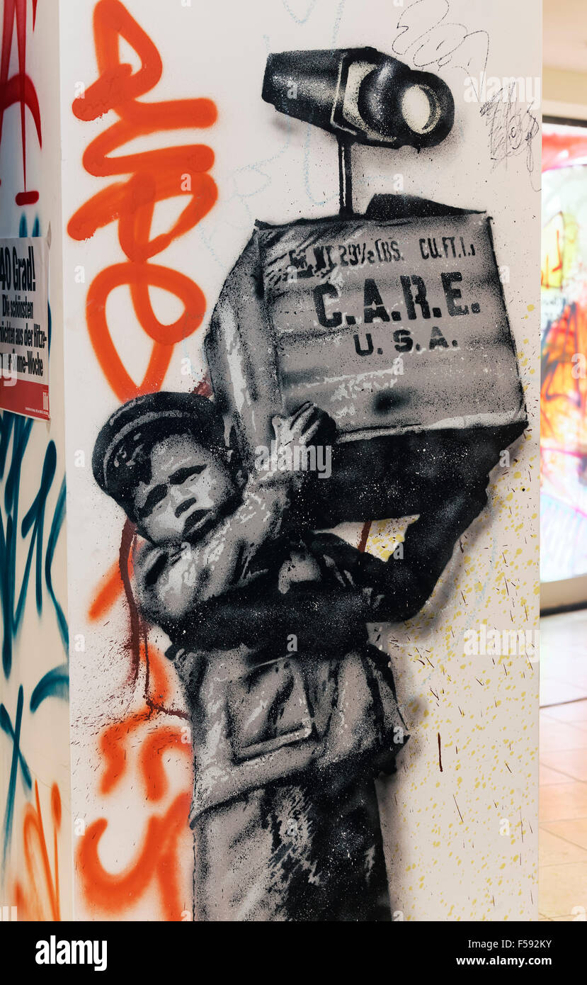 Young boy carrying US-care package with surveillance camera, spy, graffiti, street art, 40 Grad Urban Art Festival, - Stock Image