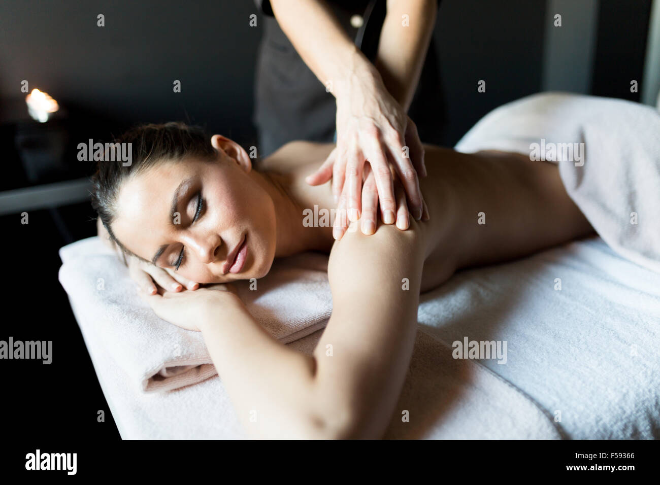 Beautiful, young and healty woman having her shoulder and body massaged by a professional masseur at a spa center - Stock Image