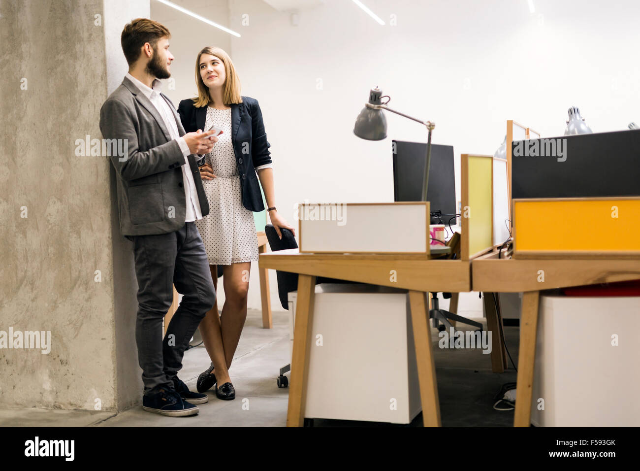 Colleagues using phone in an office and talking Stock Photo