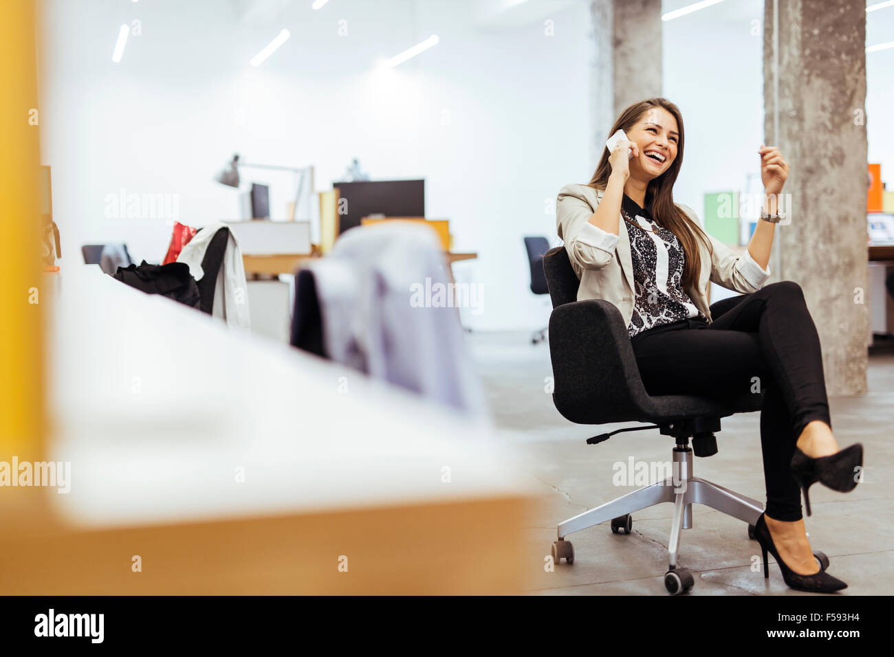 Confident business woman using phone in an office - Stock Image