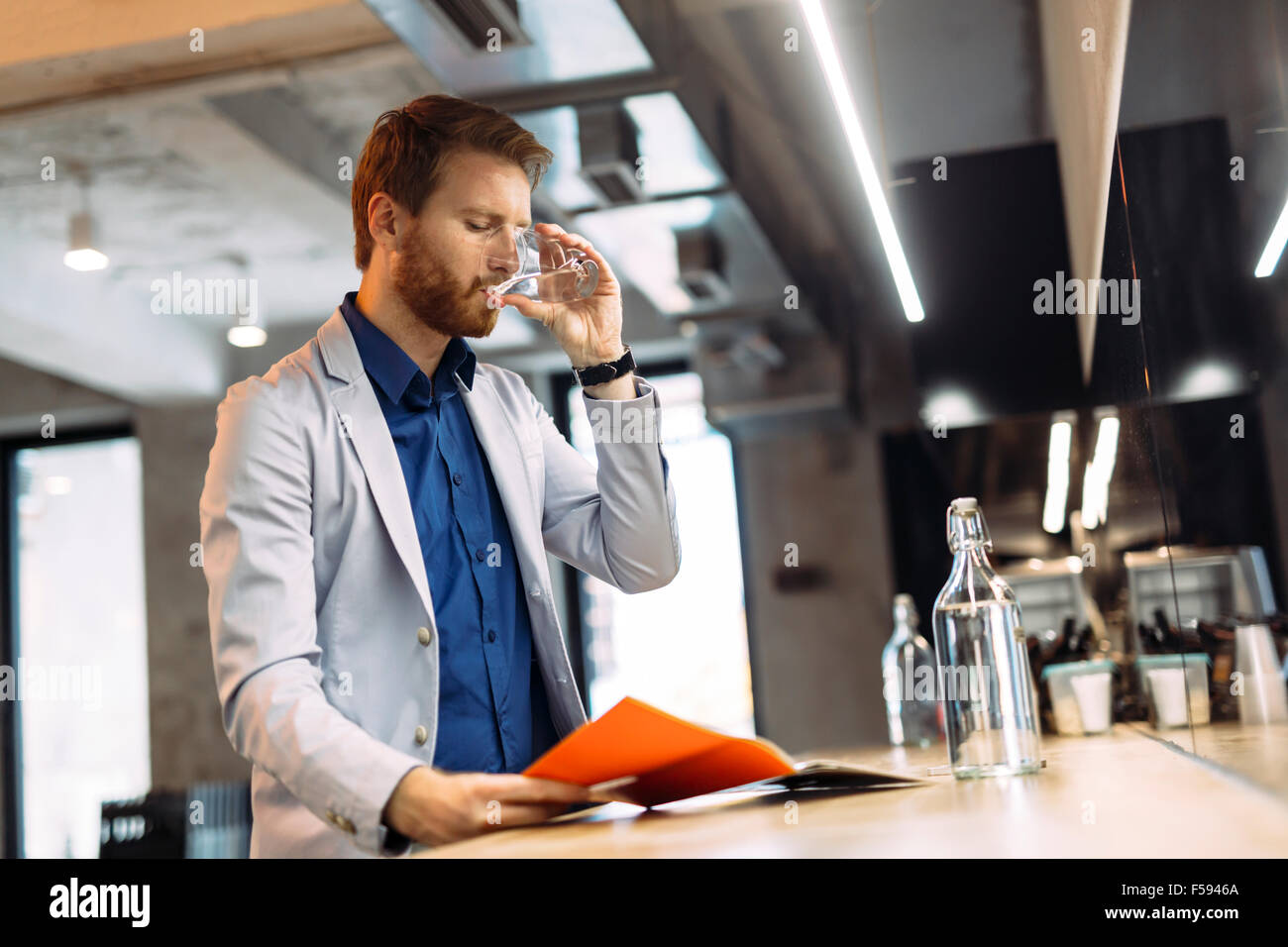 Businessman drinking water and reading paper during break - Stock Image