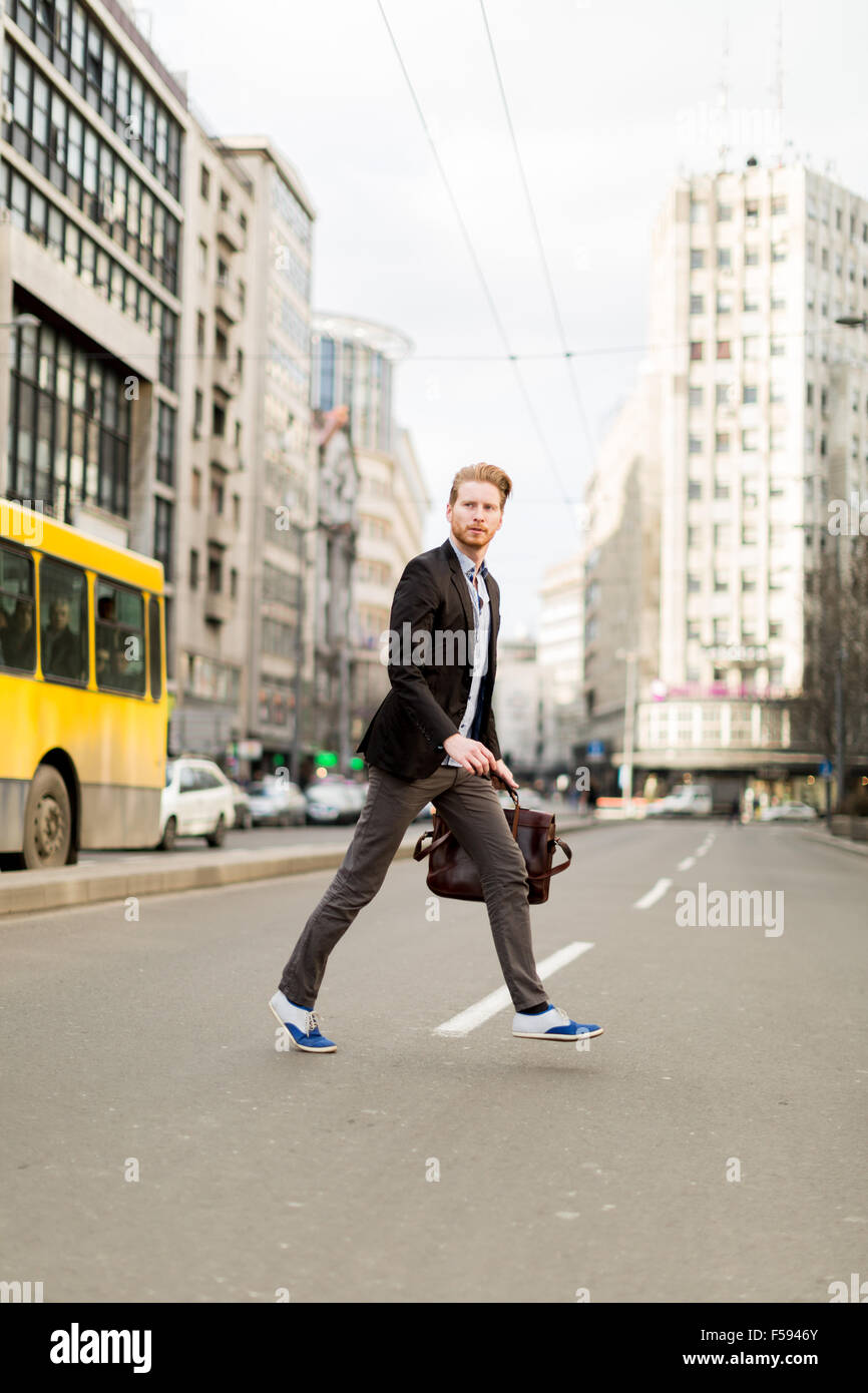 Businessman rushing accross the road in a hurry - Stock Image