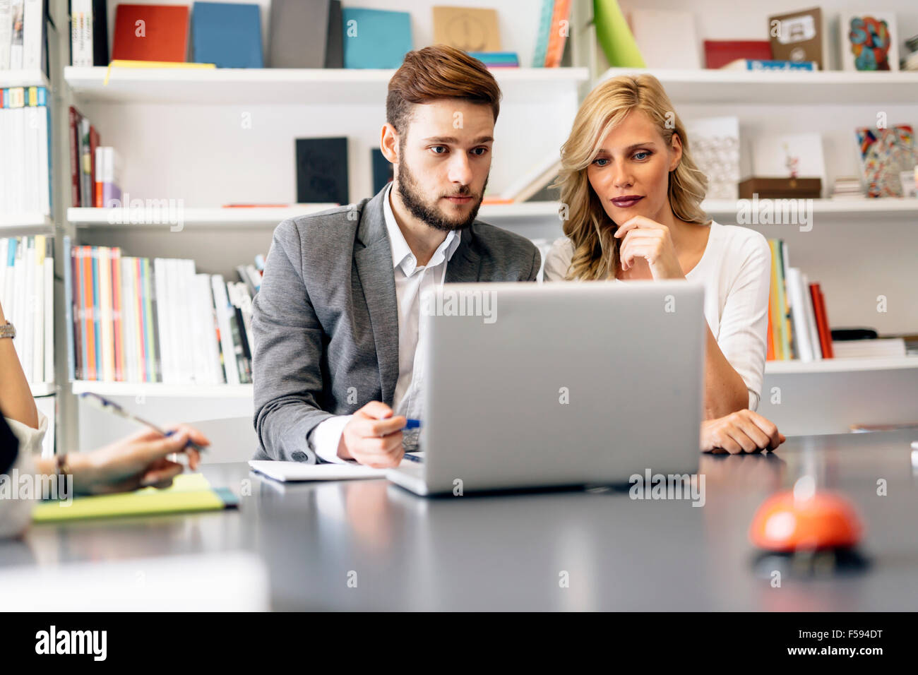 Two colleagues trying to solve problem on laptop - Stock Image