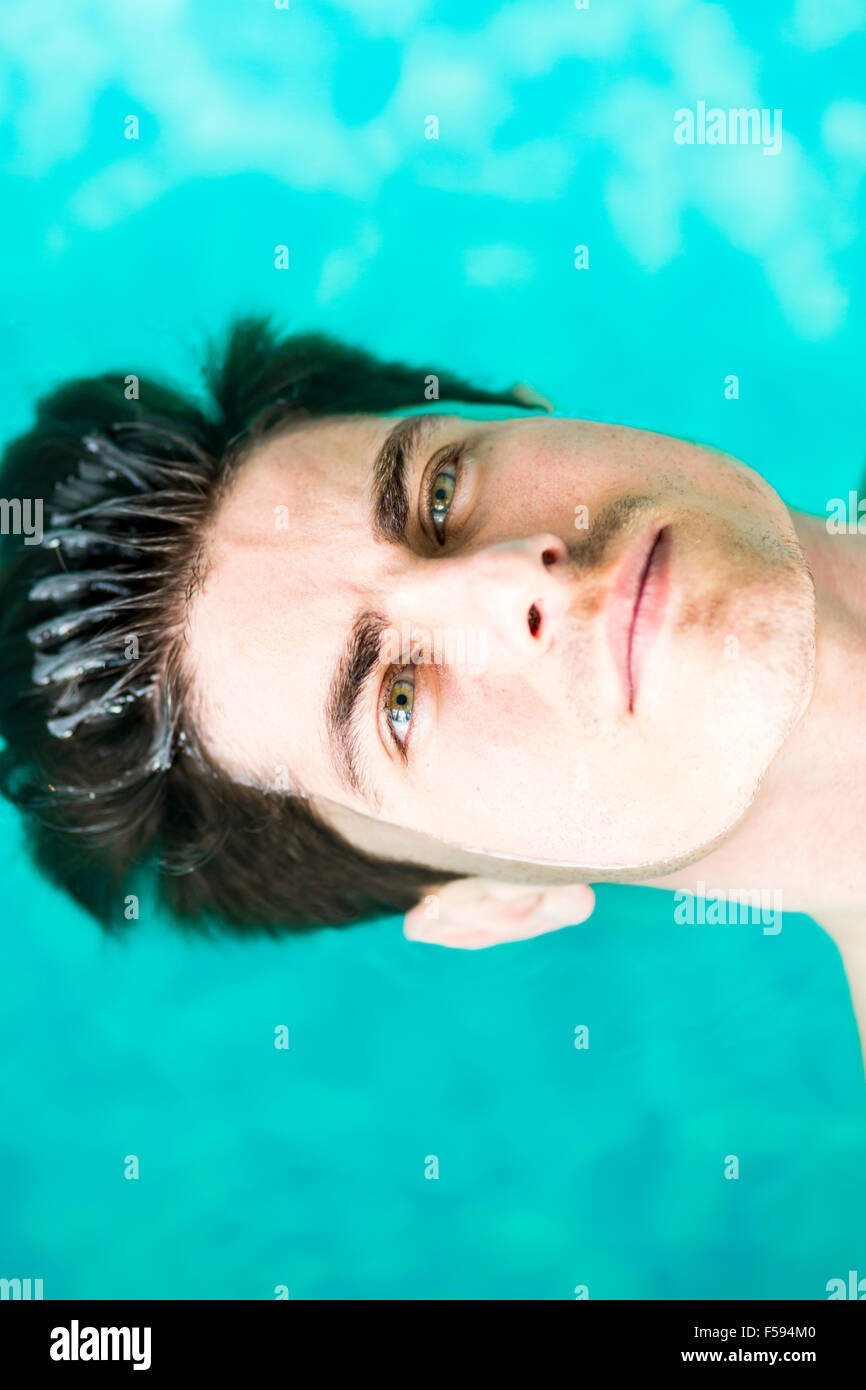 Portrait of a handsome man floating on the water surface - Stock Image