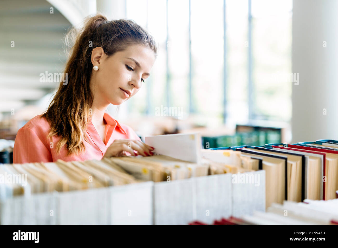 Beautiful female student takes the right book off the shelf - Stock Image
