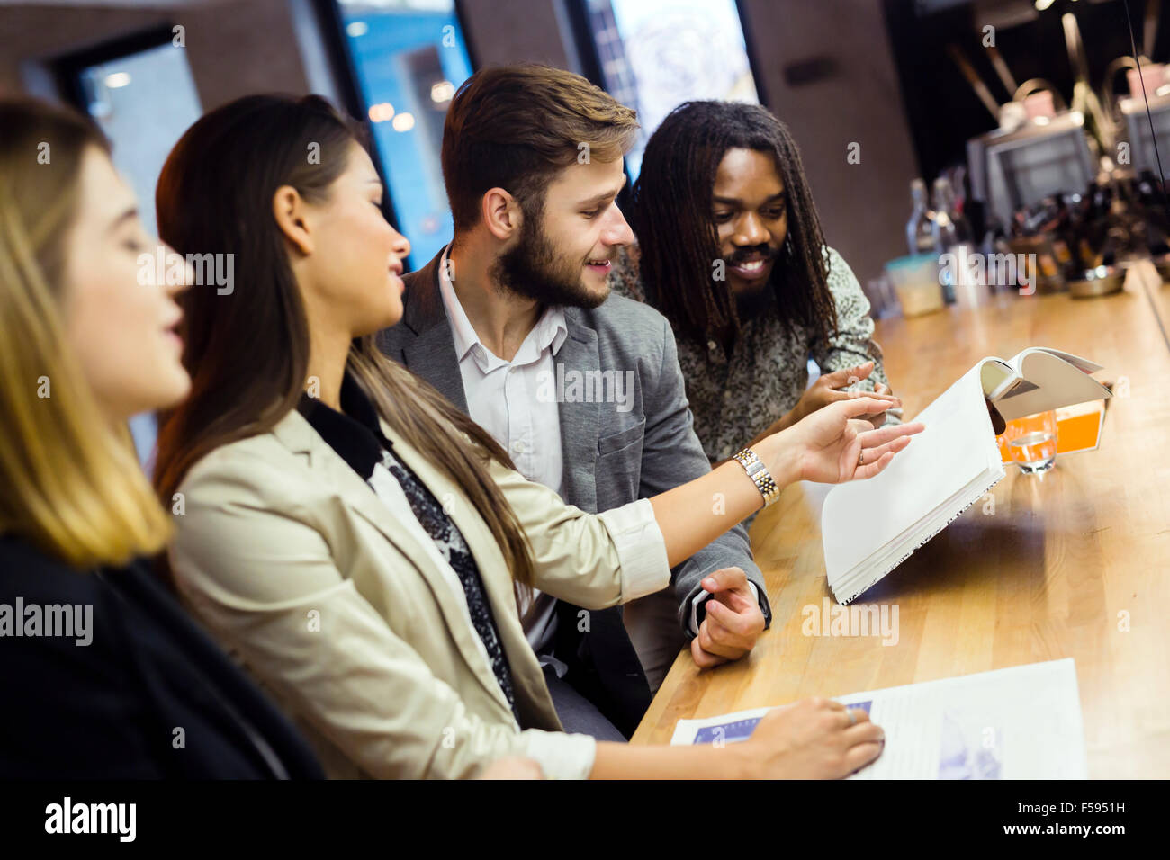 Colleagues reading articles in a pub and discussing the contents - Stock Image