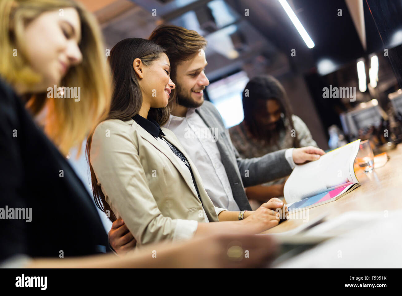 Business people in a pub relaxing and having fun - Stock Image