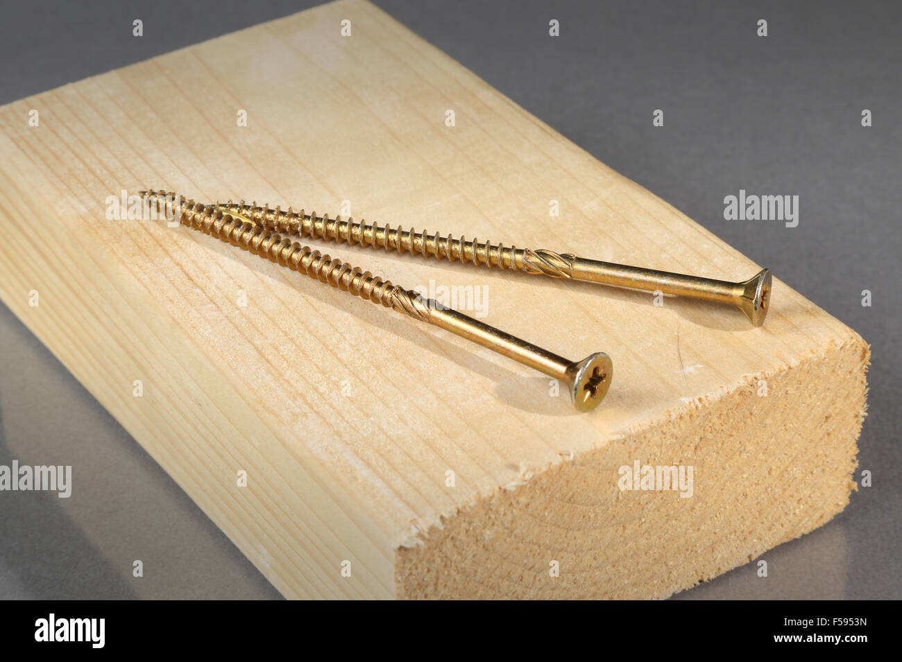 two brass wood screws shown on a block of timber - Stock Image