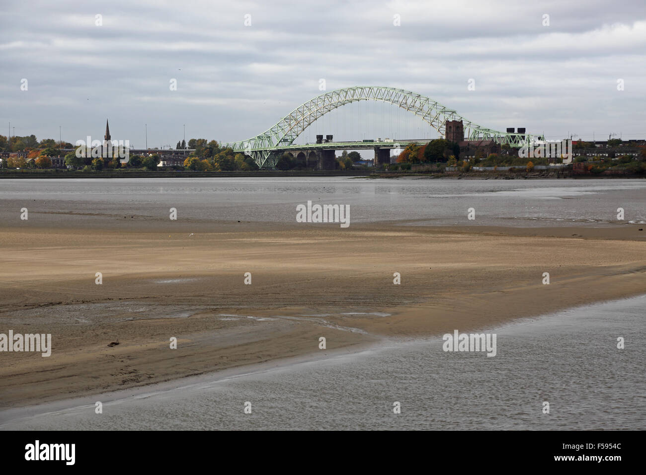 The Silver Jubilee Bridge across the River Mersey at Runcorn viewed from the east showing mudflats of the Mersey - Stock Image