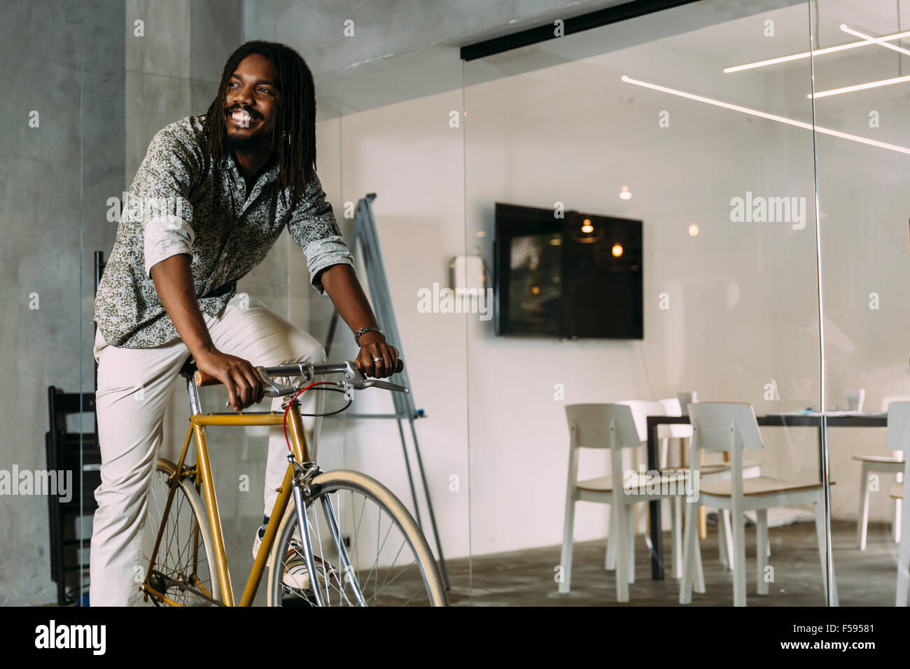 Businessman riding a bicycle to work - Stock Image