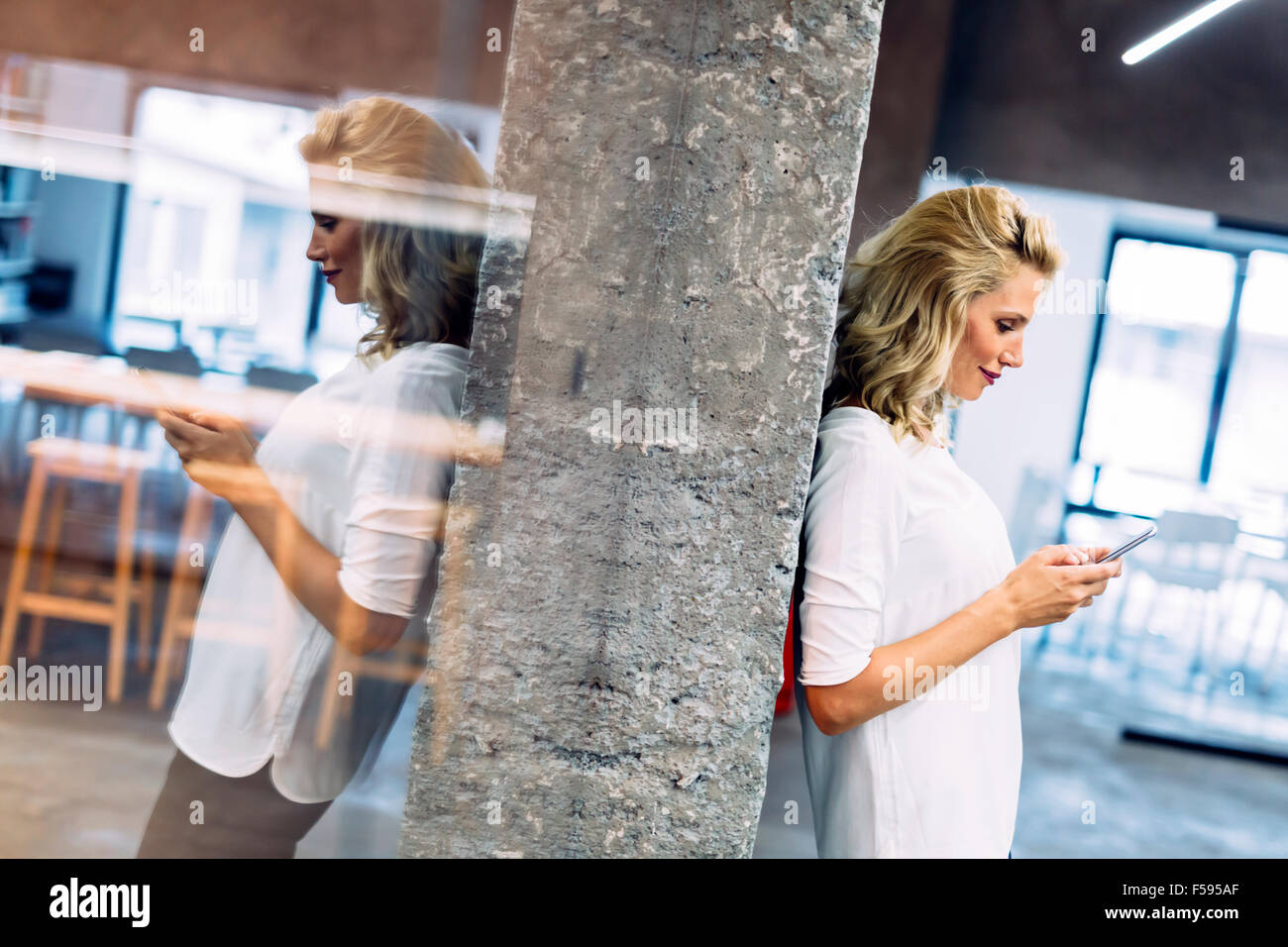 Beautiful woman using mobile phone to write message - Stock Image