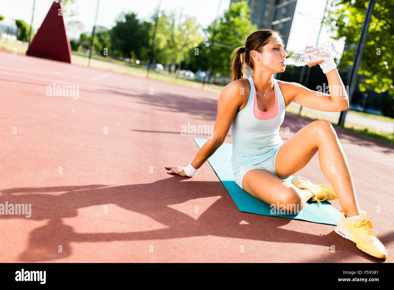 Young beautiful woman drinking water after exercise in a city training court on a sunny day Stock Photo