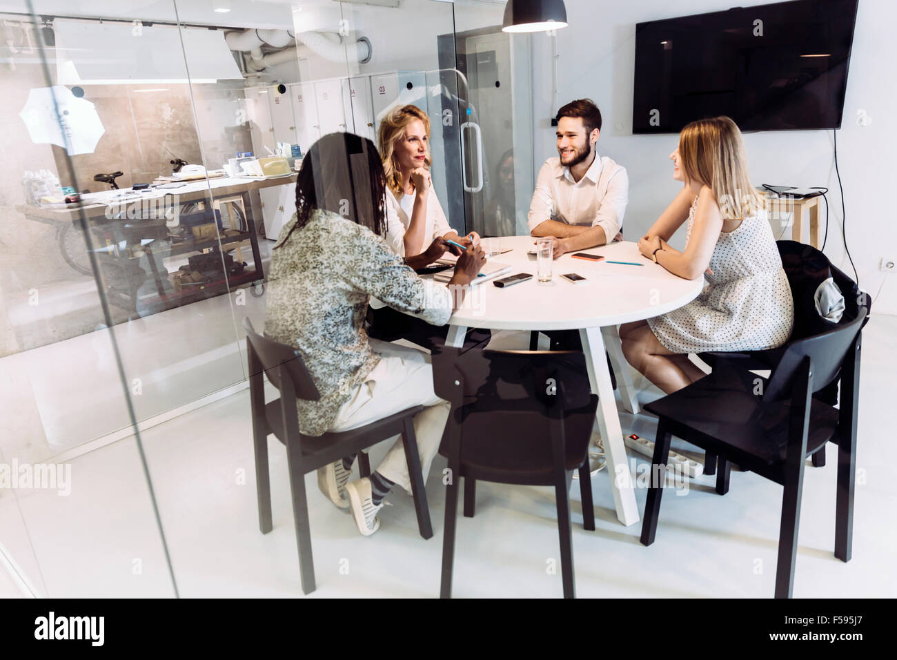 Coworkers having a meeting while sitting at a beautiful office table - Stock Image
