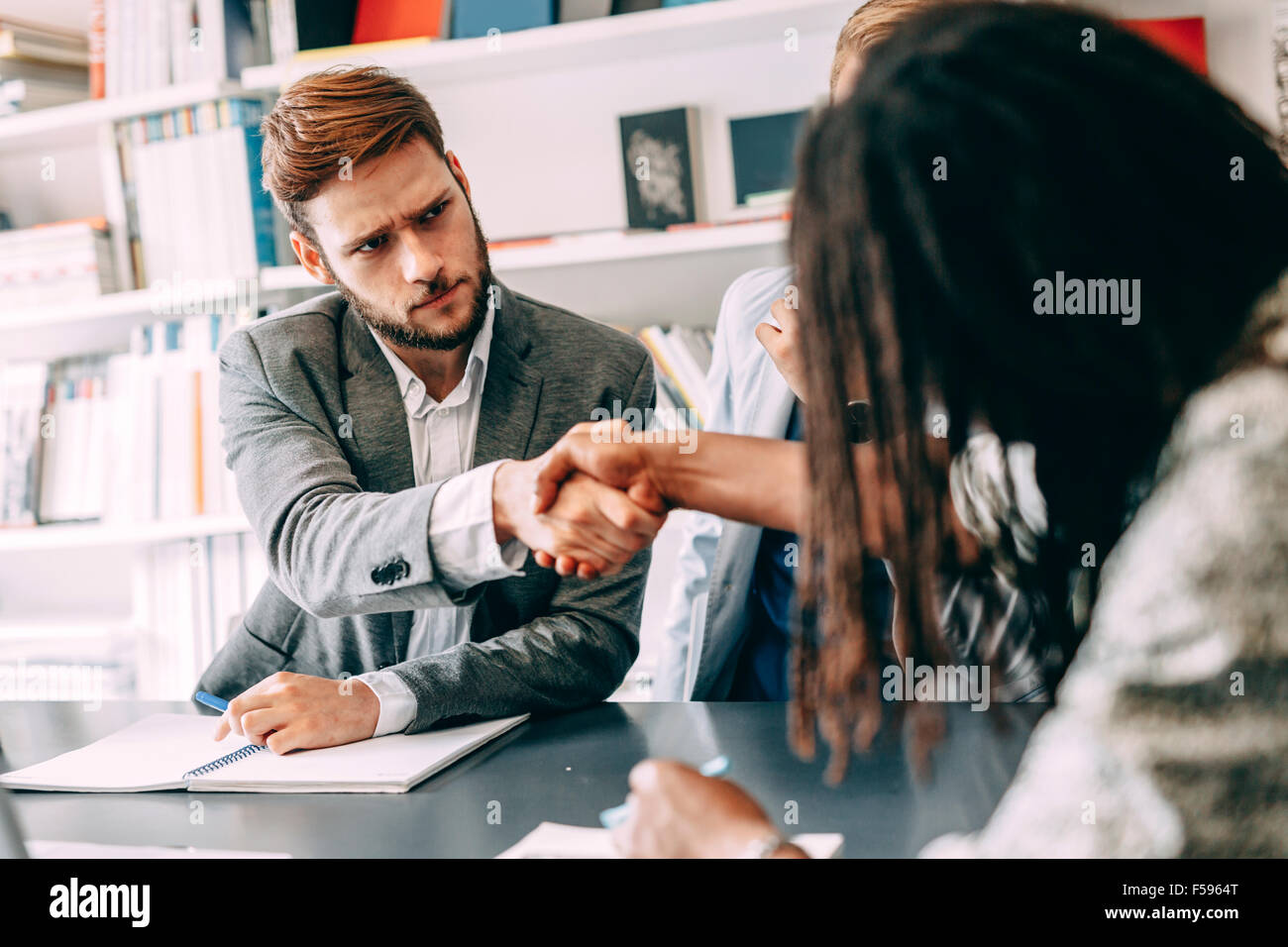 Business shaking hand with a client in office - Stock Image