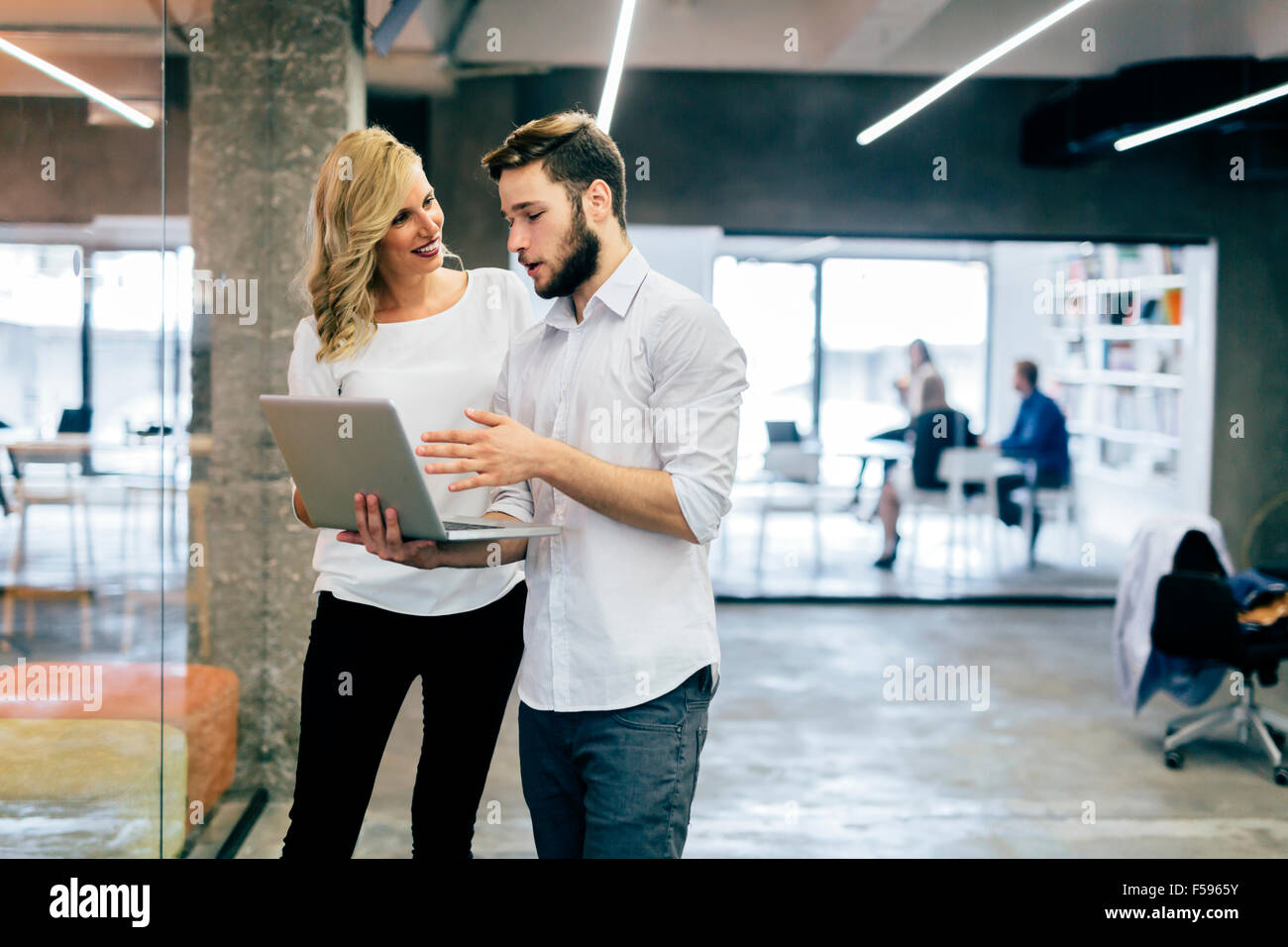 Business coworkers discussing new ideas and brainstorming in a modern office - Stock Image