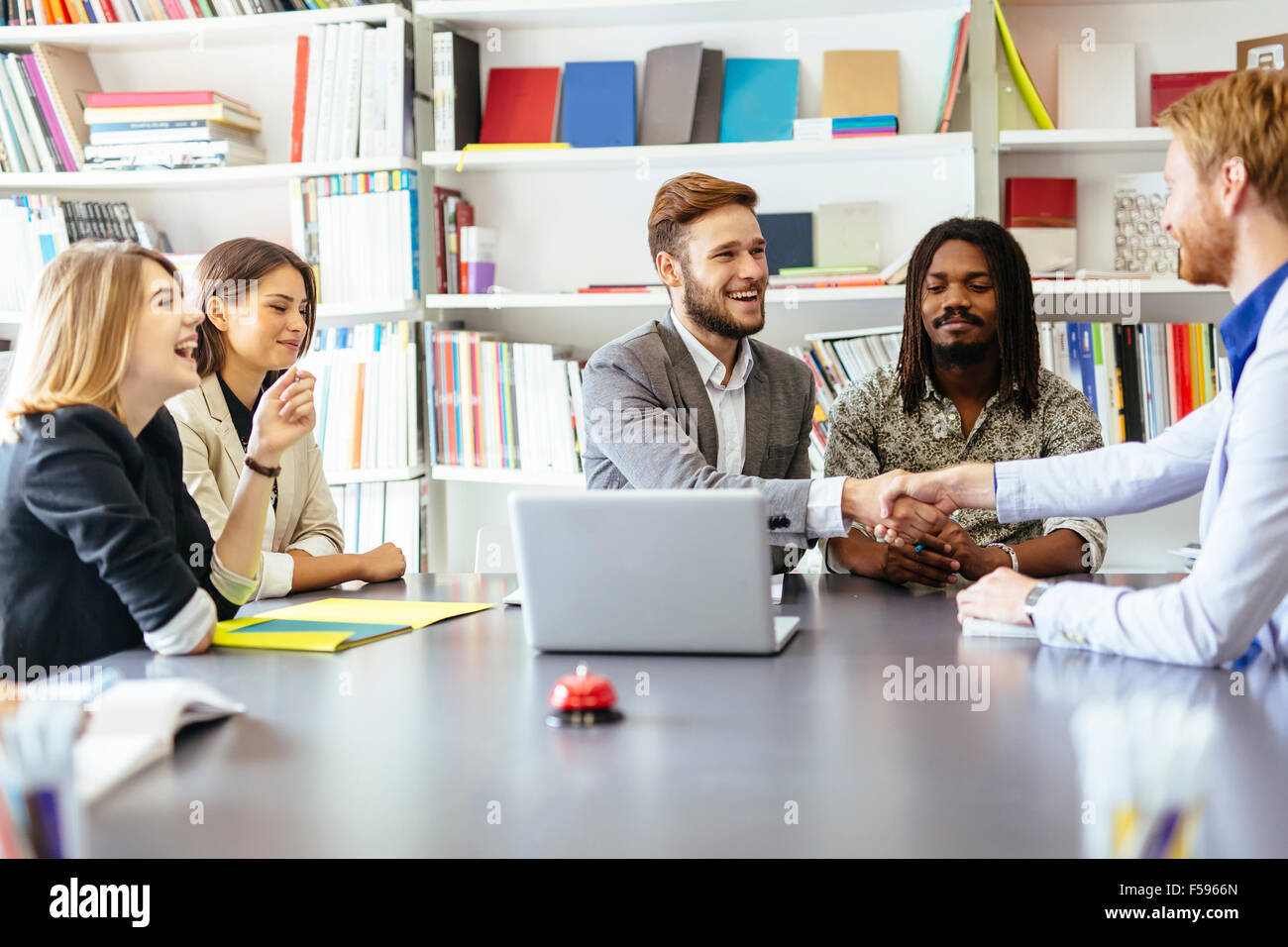 Businesspeople shaking hands in office with coworkers and staff sitting at the table with them - Stock Image