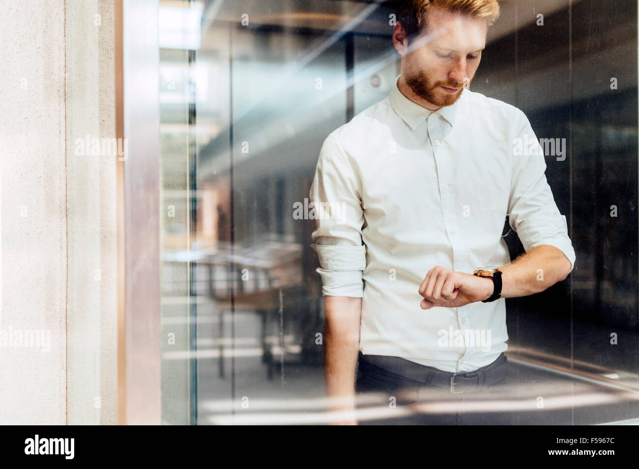 Businessman checking watch while standing in glass covered elevator - Stock Image