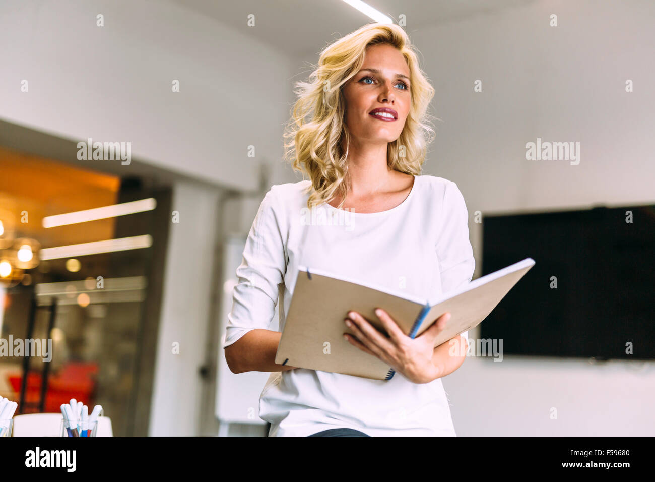 Beautiful woman educating herself by reading books - Stock Image