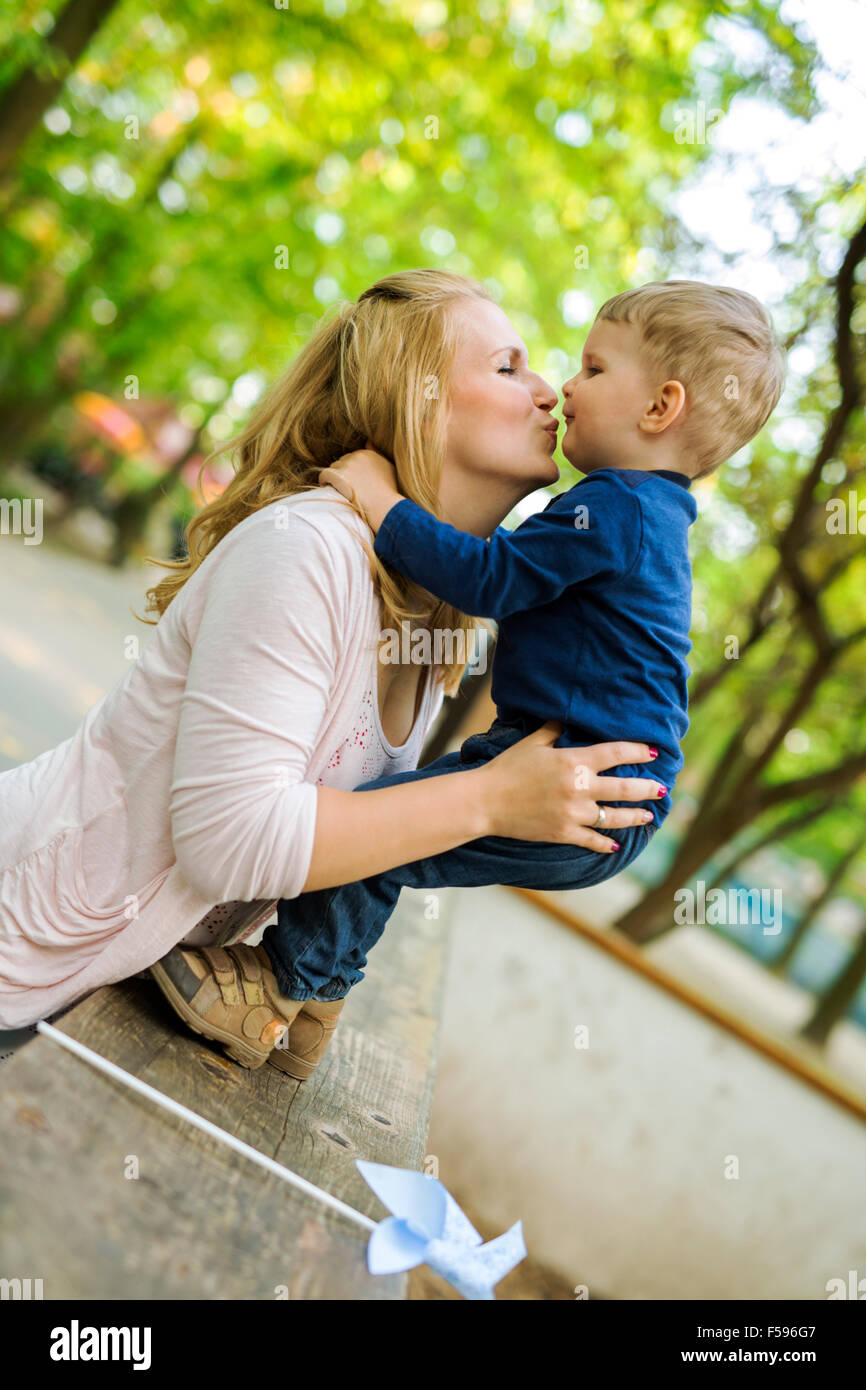 Beautiful young mother with her handsome little son in a park Stock Photo
