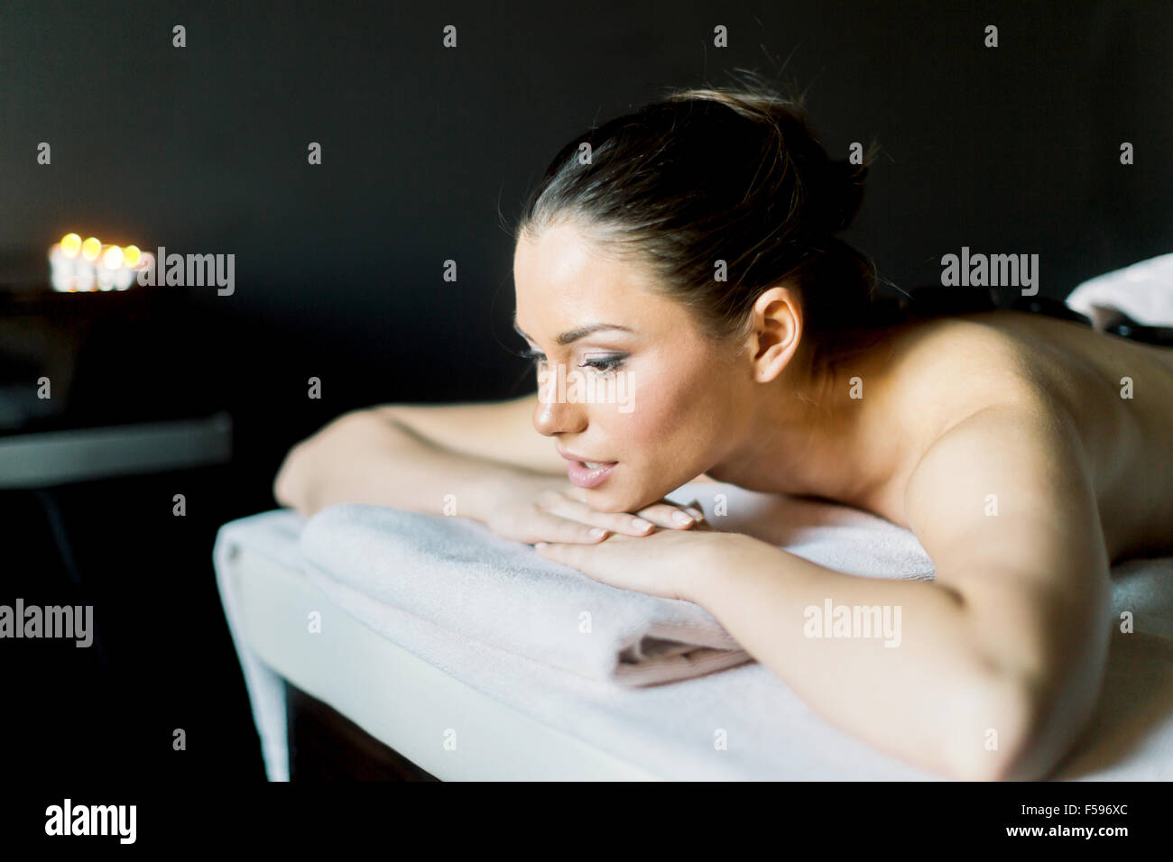 Portrait of a young and beautiful woman  relaxing with eyes open on a massage table in a dark room with candlelight - Stock Image