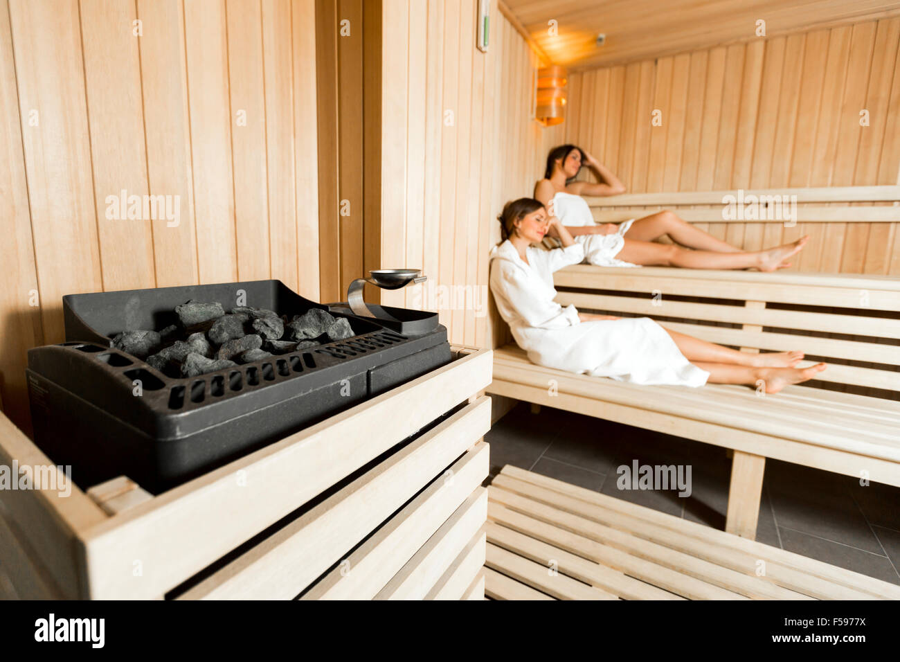 Sauna heater in a cozy sauna and girls relaxing in the background - Stock Image