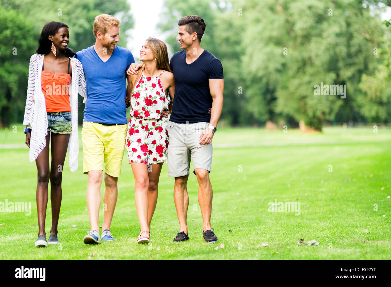 Cheerful friends walking in nature outdoors and having a good time - Stock Image