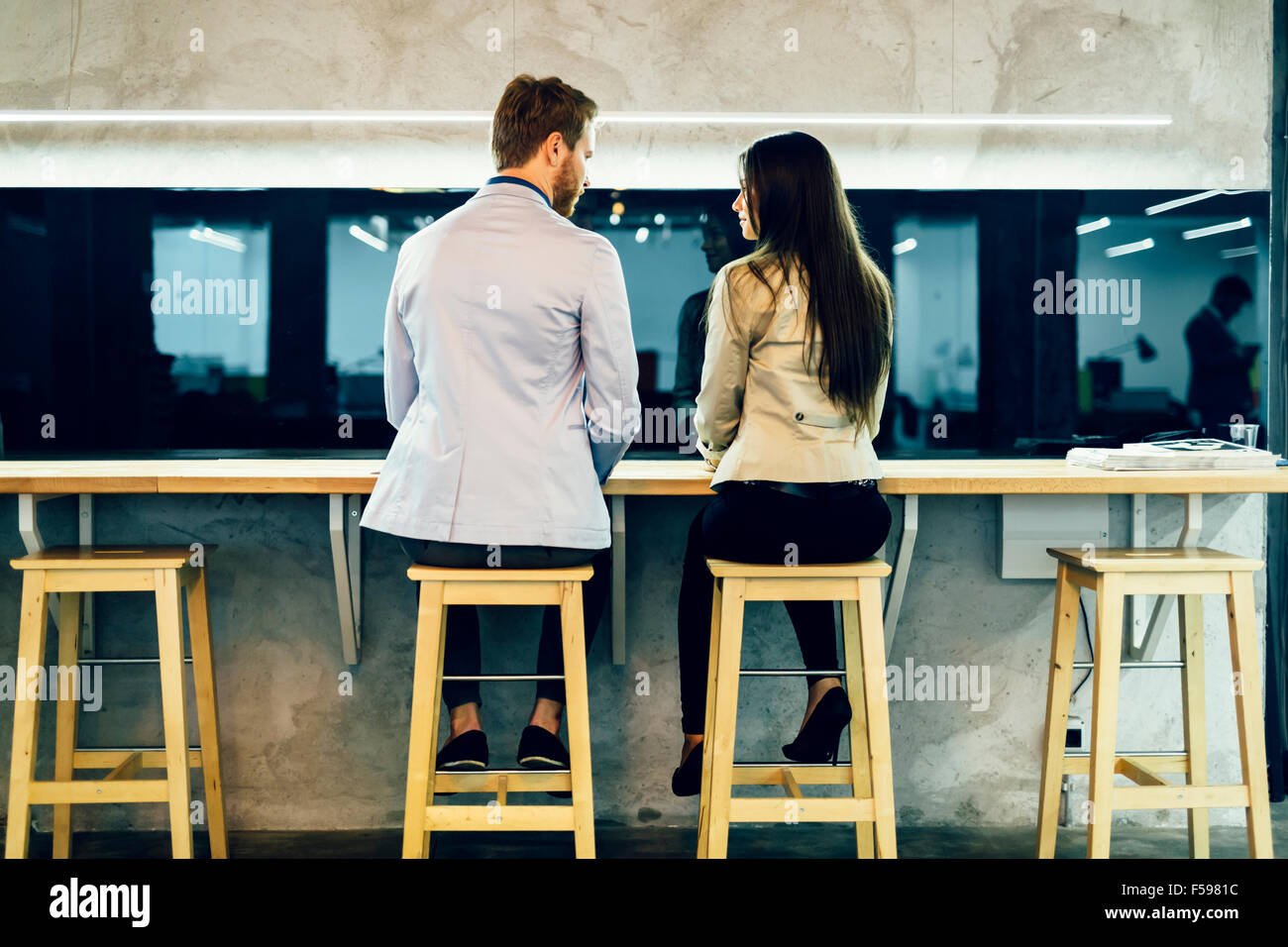 Young colleagues conversing during break hours in a restaurant - Stock Image