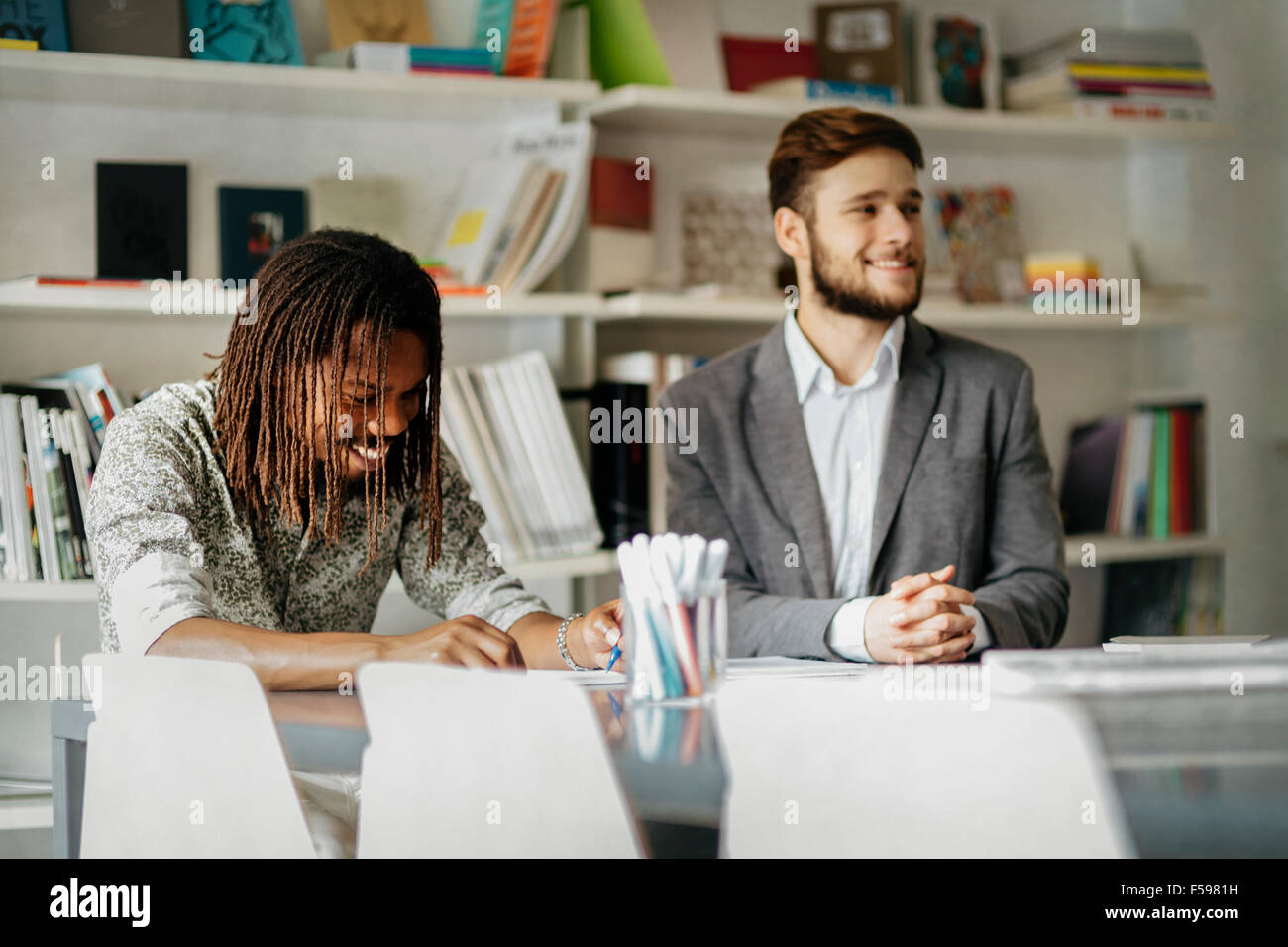 Students preparing for exams by studying in library - Stock Image