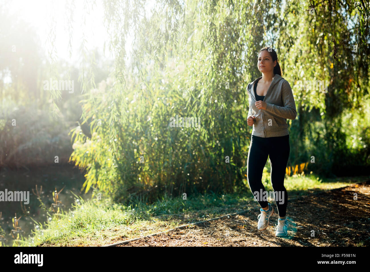 Sporty girl jogging in park close to a river - Stock Image