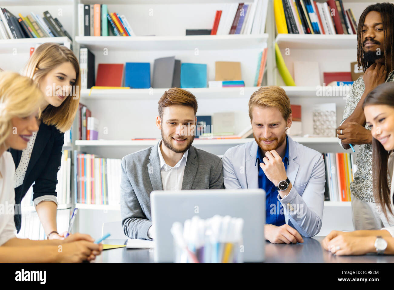 Colleagues brainstorming in office while pointing out new ideas on laptop - Stock Image