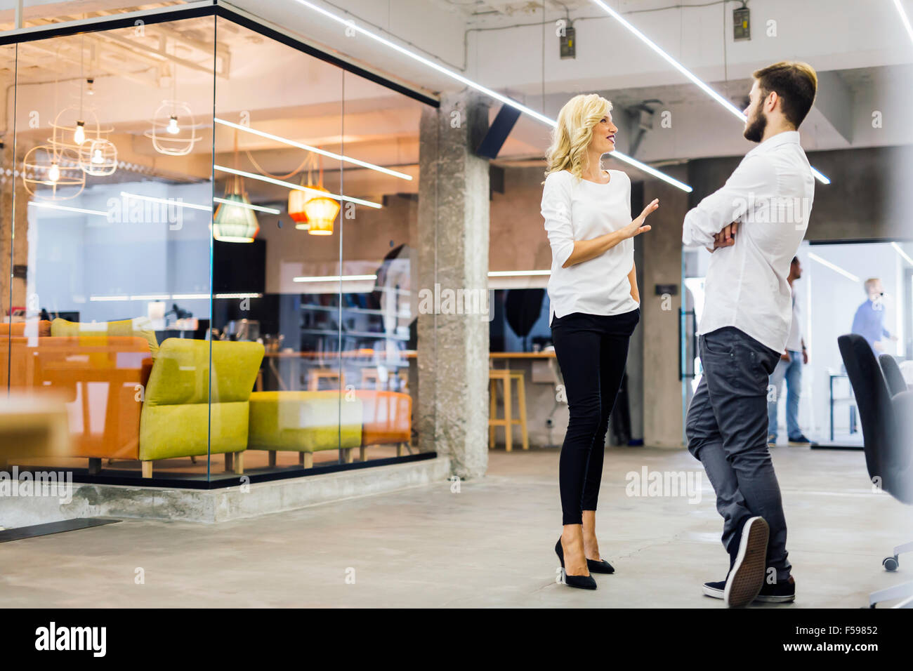 Office talk between colleagues at work - Stock Image