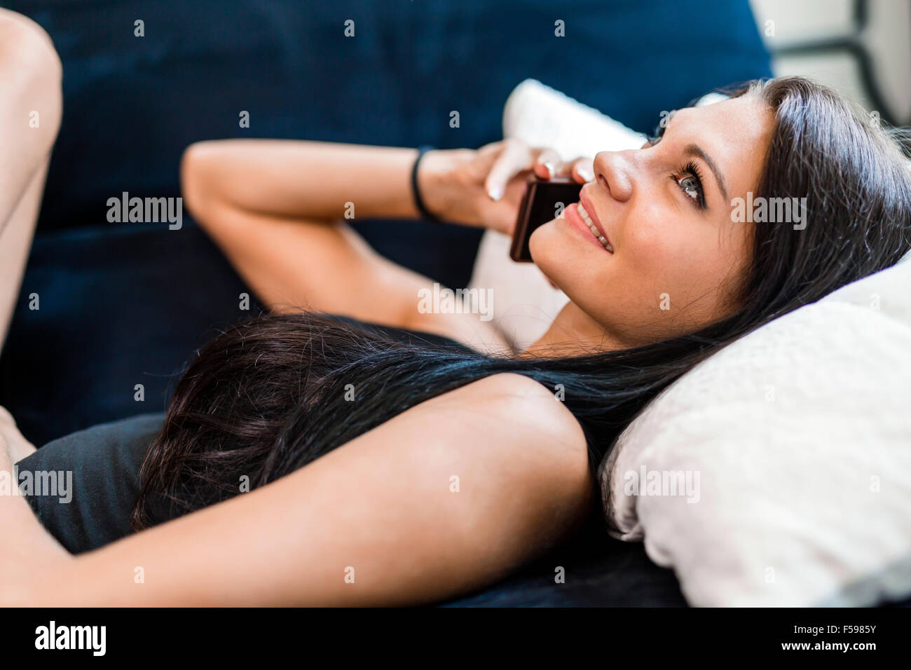 Closeup of a beautiful young woman talking on the phone while lying in bed and smiling - Stock Image