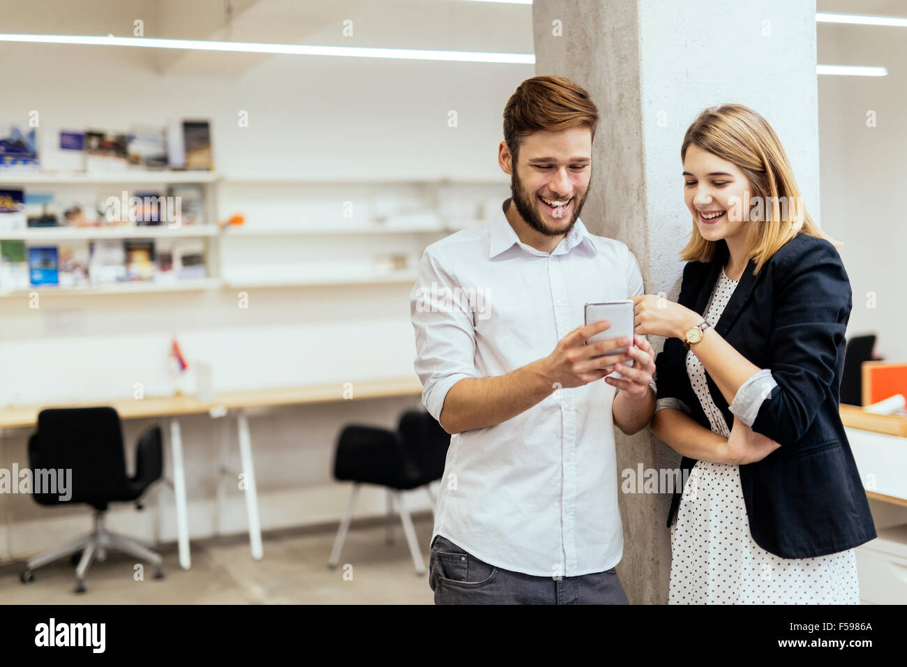 Two colleagues smiling while looking at the phone in a beautiful office Stock Photo