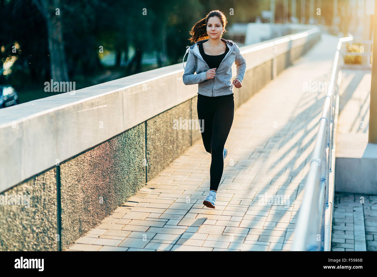 Sporty woman jogging in city to keep her body and soul in shape - Stock Image