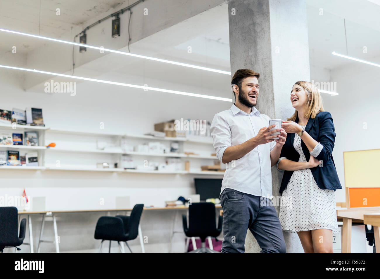 Two colleagues having a laugh in an office after look at the phone content - Stock Image