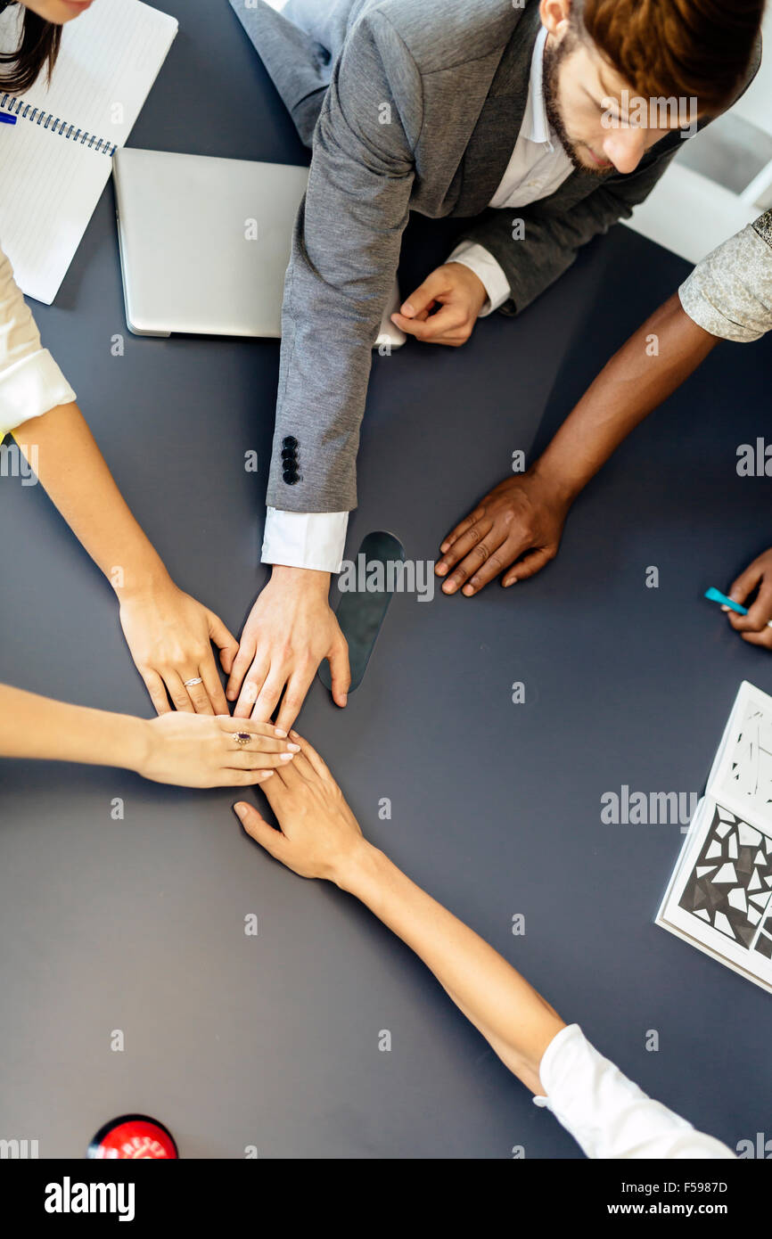 Dedication and teamwork lead to success - colleagues putting their hands to gether to represent unity - Stock Image