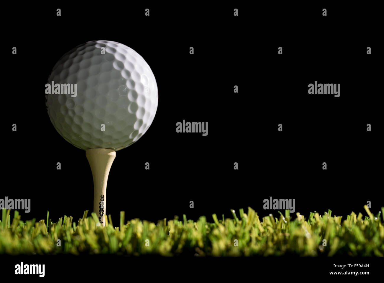 golf ball on a tee at night - Stock Image
