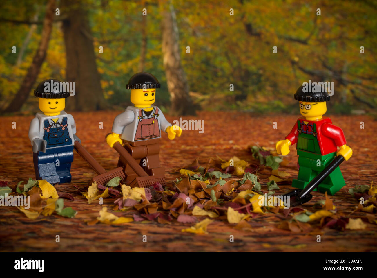 Lego men sweeping leaves - Stock Image