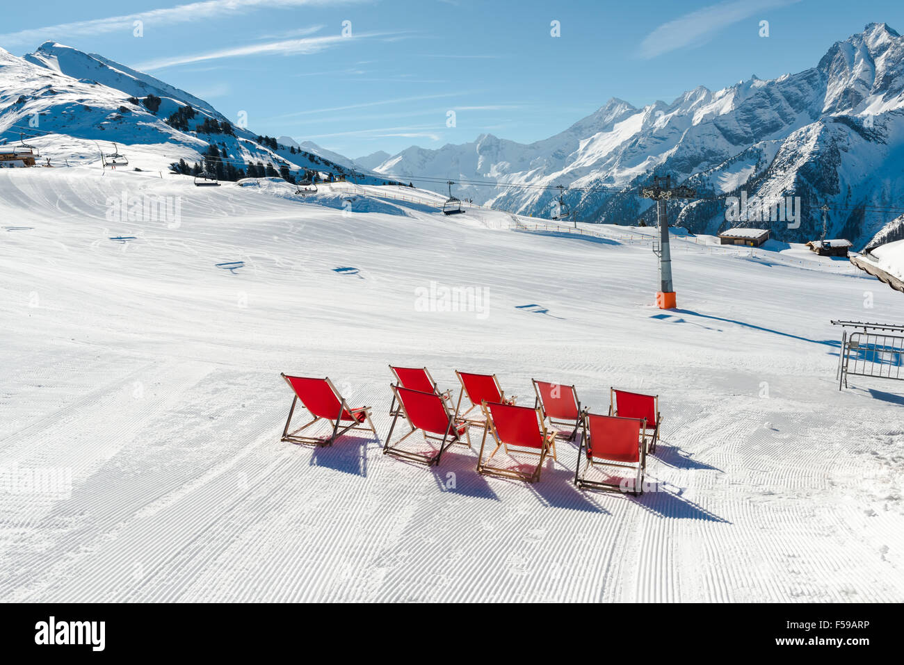 Empty red deck chairs on the snow in Mayrhofen ski resort, Austrian Alp - Stock Image