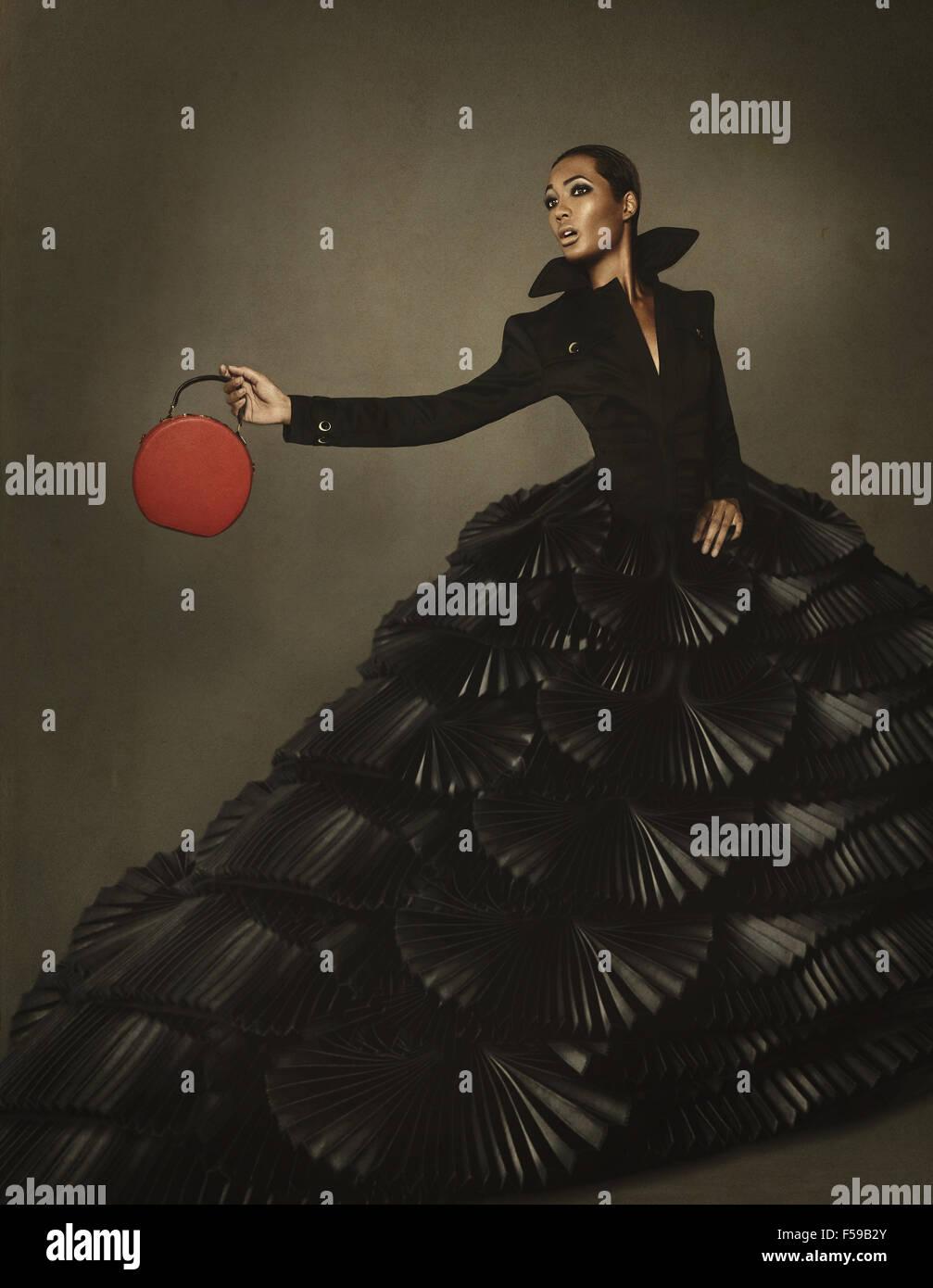 Fashion editorial model in avant garde gown, holding handbag Stock ...